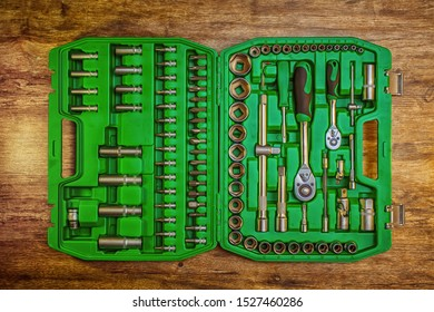 Open toolbox with different instruments on wooden workbench. Set of different working tools on wooden background. Top view. Hand tool. Tools male workplace background texture dark wood.