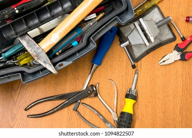 open toolbox, small portable vice screwdriver tools for repair  randomly scattered on the work surface