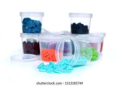 Open transparent plastic container with colorful plastic snap fastener buttons spilling out with other filled containers in background