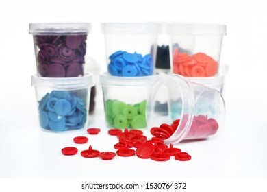 Open transparent plastic container with red plastic snap fastener buttons spilling out with containers with colorful snaps in background