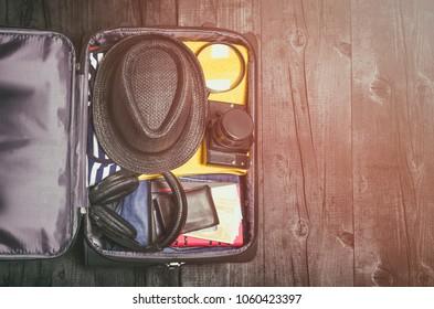 Open travel bag on wooden floor background, top view.