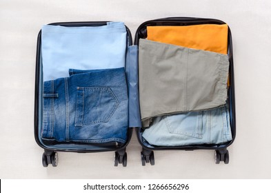 open travel suitcase with female or male clothes for a trip, top view