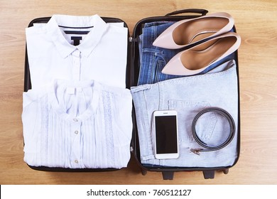 Open travel suitcase with woman trendy business clothes, accessories and smart phone on wooden floor top view close up. Packing clothes for a trip