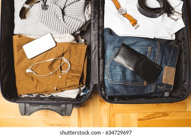 Open traveler's bag with men clothing, accessories, wallet, watch, belt and ear phones. Travel and vacations concept.