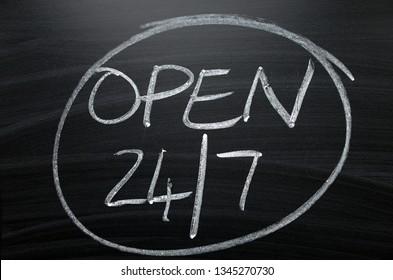 Open twenty four hours by seven written by hand in white chalk on a blackboard sign