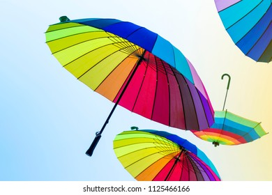 Open umbrellas with bright colors of the rainbow fly on yellow-blue pastel background. Umbrellas flying in the sky with the colors of Pride Day. LGBT party.