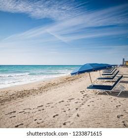 Open umbrellas on the sandy shore near the ocean. Beach in Miami, Florida. Empty beach. Seaside. Early morning. Clouds