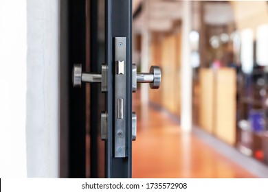 Open unlocked doors in an empty secure vacant corporate business area, nobody, door knob lock side closeup. Door left open, office building security abstract concept.  Simple entrance and a hallway