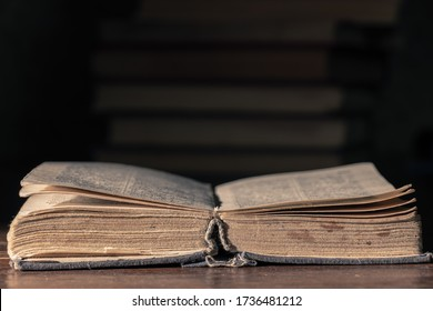 Open very old book on a wooden table against the background of a stack of books