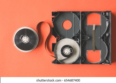 Open video cassette tape on orange background.