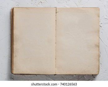 Open vintage book blank on white concrete background. Top view or flat lay. Copy space.