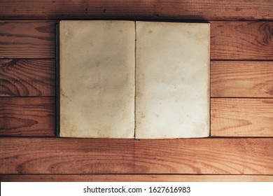 Open Vintage book on a red wooden table background. Top view.