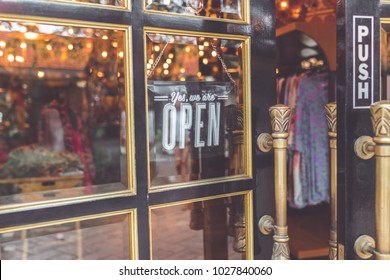 Open vintage sign broad through the glass of store window. Asia.