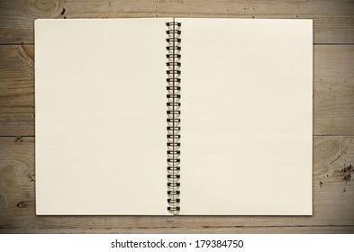 An Open vintage sketchbook or notebook on old wooden table.