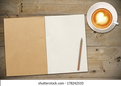 An Open Vintage Sketchbook or Notebook with pencil and latte art coffee on Old Wooden Table.
