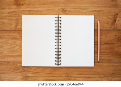 An Open vintage sketchbook or notebook with pencil on modern wooden table