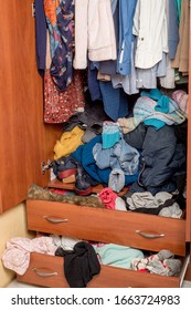 open wardrobe with clothes on hangers and clutter in open drawers. Close-up