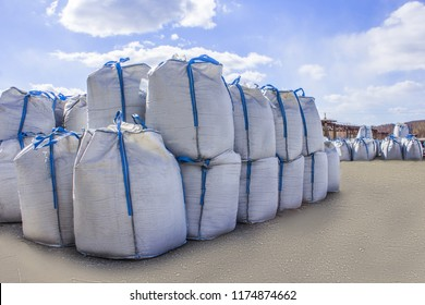 open warehouse of big bags against the blue sky and clouds.