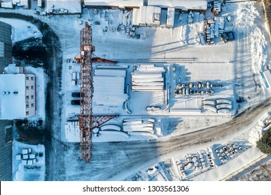 Open warehouse for storage of large diameter metal pipes. A gantry crane is installed in the territory. Winter sunny day. Aerial view.