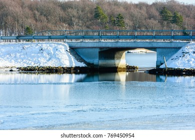 Open water flow under a small viaduct or bridge and thin ice cover the surrounding water.