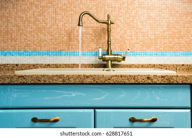 Open water tap bronze on a ceramic tile background