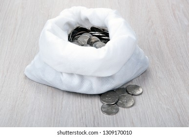 open white bag with russian ruble coins on a wooden background close up
