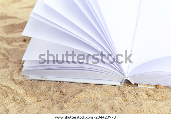 Open white book on sand background