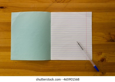 Open white lined exercise book with green cover and blue pen on a light orange wooden study table atop