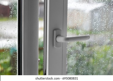 Open white plastic window. In the rainy weather. Closeup.