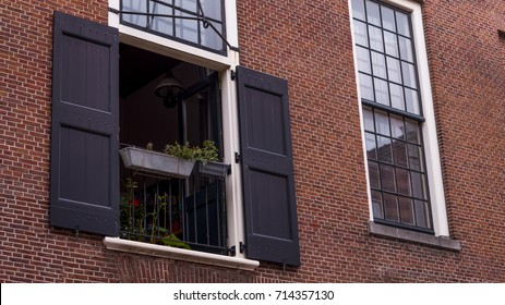 a open window with open black shutters and a black rail with a plant pot hanging from it on a brick background