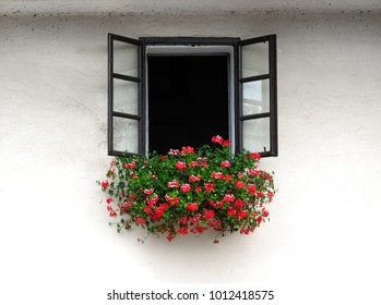 Open window decorated with beautiful bright geranium flowers on white wall of stone building