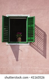 Open window with flower vase with green shutters located in a Zagreb neighborhood.
