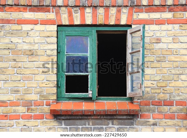 Open window with green frame and missing glass