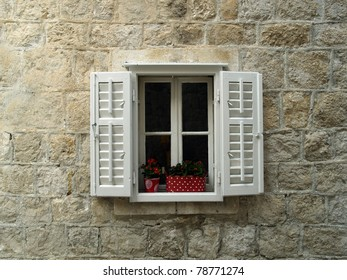 Open window with jalousie on stone wall