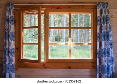 Open window with natural wooden frame and blue flower curtains. Morning forest view. Sunrise in the country.