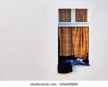 Open window, old clothes, torn curtain. Hanging laundry outside