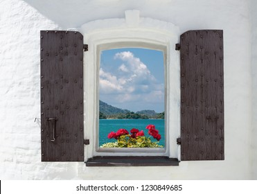 Open window in an old house decorated with flowers and sea view
