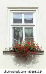 The open window with red flowers on a sill in Krakow old town (Poland).