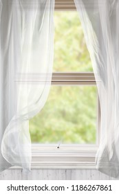 Open window with voile curtains blowing in the breeze