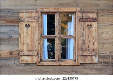Open window of a wooden hut with hearts in the blinds