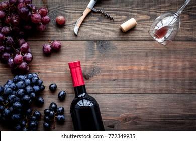Open wine bottle. Grape and corkscrew on dark wooden background top view copyspace