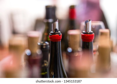 open wine bottles, flexible wine pourer, glasses, corks with blurred background at the wine tasting event