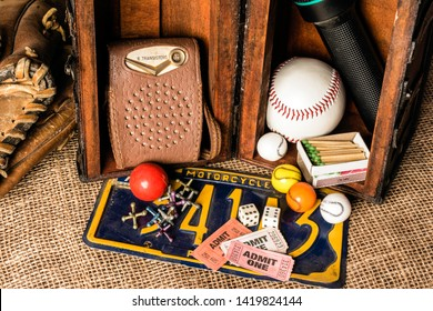 open wood chest showing young boys treasures baseball transistor radio matches bubble gum jacks dice tickets baseball glove motorcycle license plate on burlap background