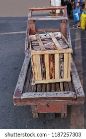 Open wooden box made of nailed slats filled with waste paper and remains of boards and pieces of wood placed on a flatbed pushcart located on the side of a street. Carbon Market-Cebu City-Philippines.