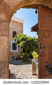 Open wooden door into green garden in old town (Rhodes, Greece)