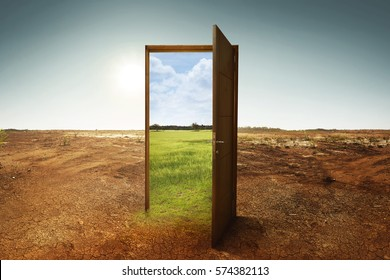 Open wooden door to the new world with green environment. Climate change concept.