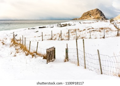 Open wooden gate to a field on a snowy beach.