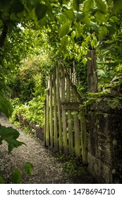 Open Wooden Gate And Gravel Footpath To Orchard