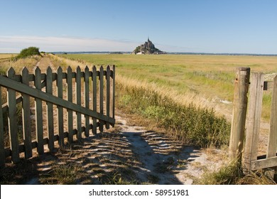 An open wooden gate leading to the fields surrounding Mont St. Michel