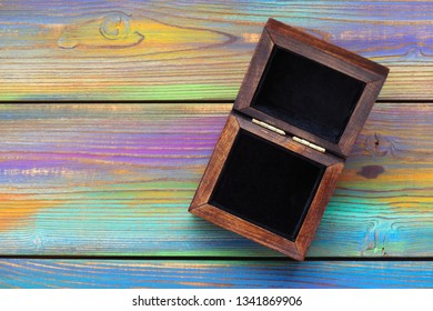 Open wooden jewelry box with black velvet inside on a bright colored wooden background. Beautiful bright background, empty space, free space for text
